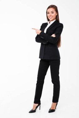 Happy business woman pointing to copyspace.