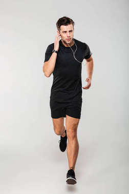 Full length portrait of a young man athlete in earphones