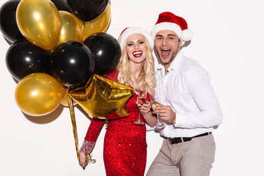 Excited happy young loving couple wearing christmas hats drinking champagne.