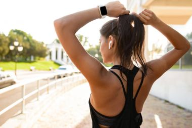 Back view of a young fitness girl in earphones