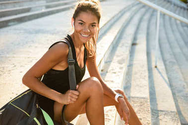 Portrait of a happy sportsgirl in earphones