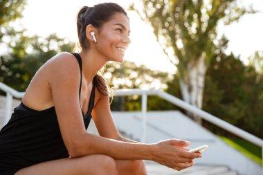 Portrait of a happy fitness girl in earphones