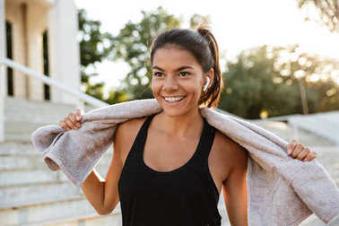 Portrait of a smiling fitness girl with towel resting