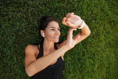 Top view of a happy fitness girl in earphones
