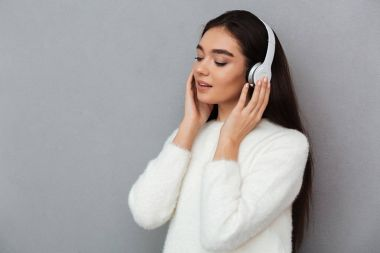 Pleased brunette woman in sweater and headphones listening music