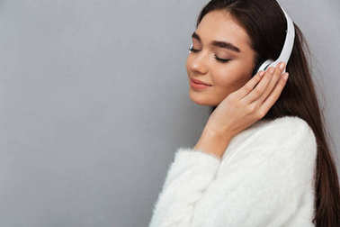 Side view of happy brunette woman in sweater and headphones