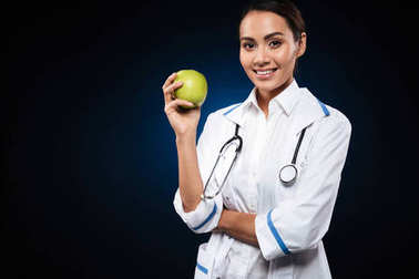 Young smiling lady doctor holding apple and looking camera isolated
