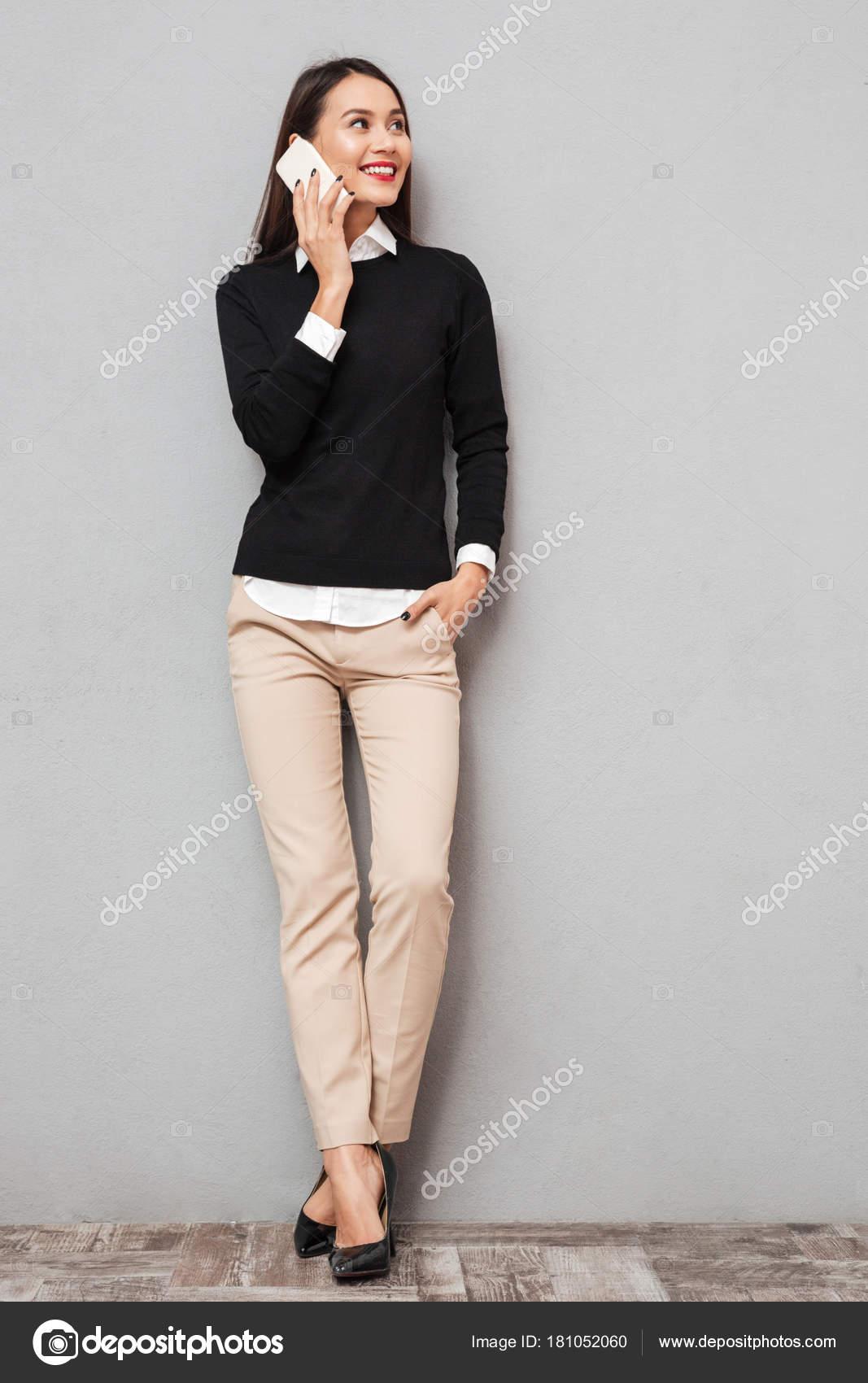 Повна довжина образ посміхаючись азіатські жінки в діловий одяг говорити  смартфон і фотографіях хтось дивитися вбік над сірий фон — Фото від  Vadymvdrobot a7ee0bc16a825