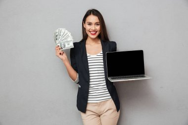 Happy business woman showing blank laptop computer and holding money