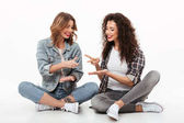Fotografie Two cheerful girls sitting on floor together and having fun
