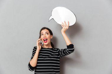 Portrait of a pretty woman holding blank speech bubble