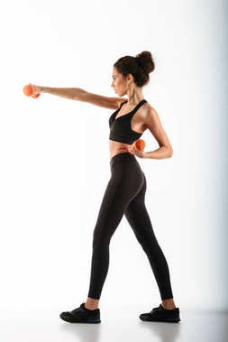 Full length image of Concentrated fitness woman standing in profile