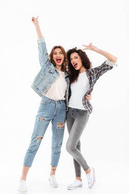 Full length image of two joyful girls standing together