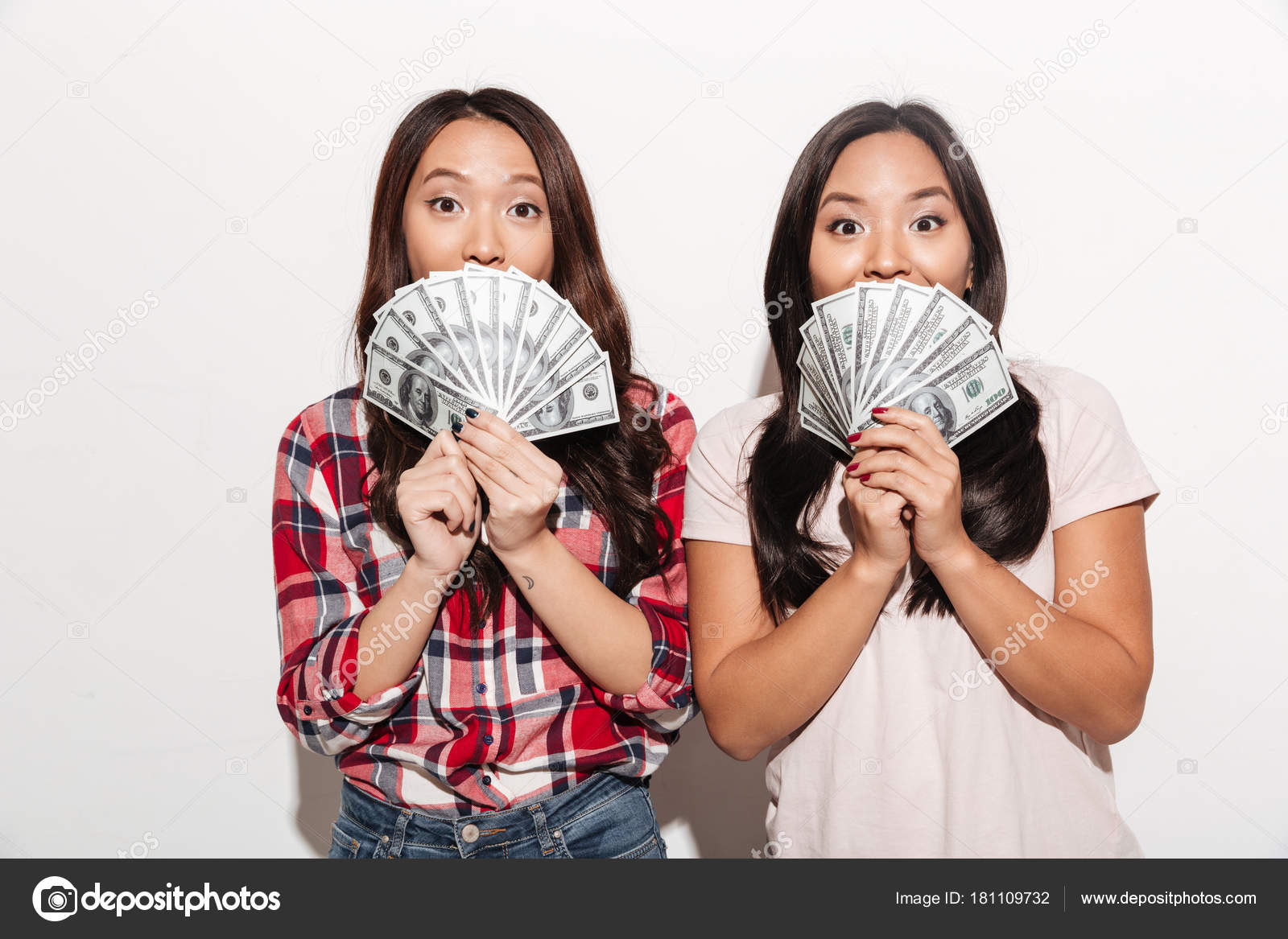 two asian pretty cute ladies covering faces with money. — stock