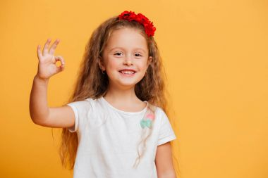 Funny little girl child showing okay gesture.