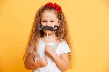 Funny little girl holding fake moustache looking camera.