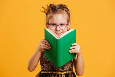 Cute girl child wearing princess crown reading book.