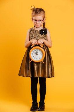 Cute little girl child holding clock alarm.