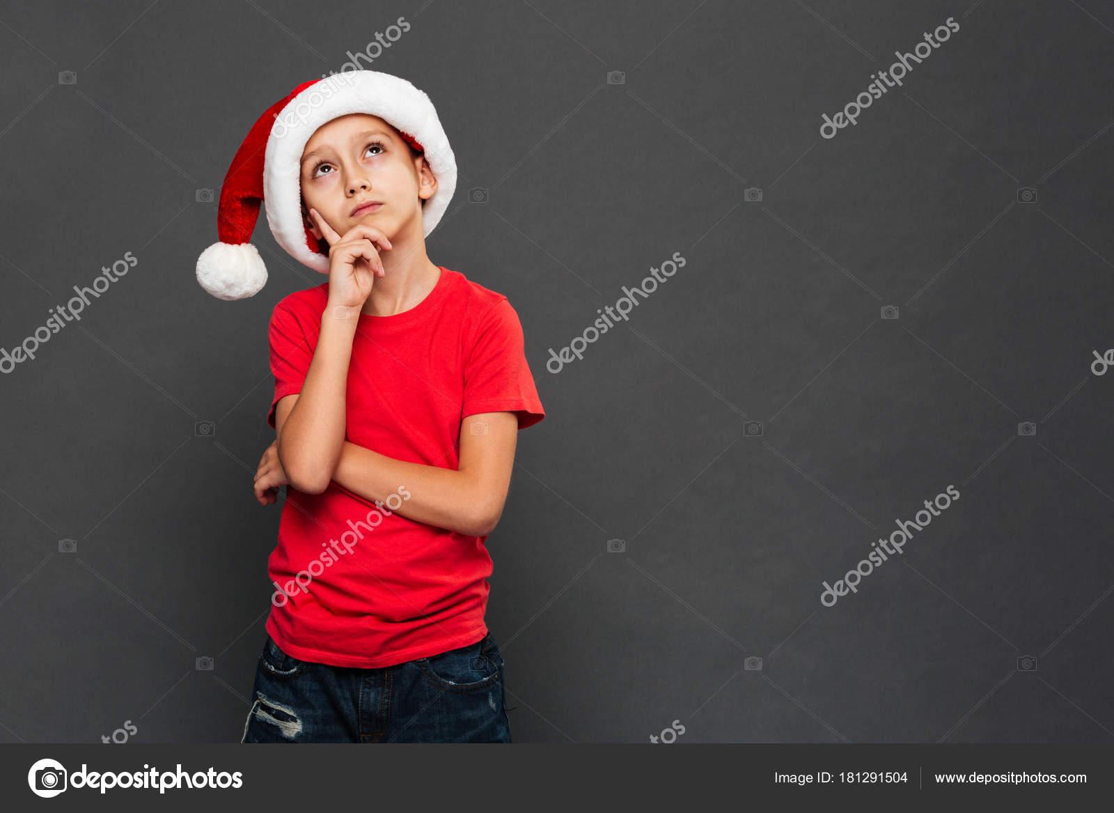 Immagine di riflessivo bimbo bambino indossa Natale cappello della santa in  piedi isolato sopra priorità bassa grigia. Che osserva da parte– immagine  stock d278b951a0c5