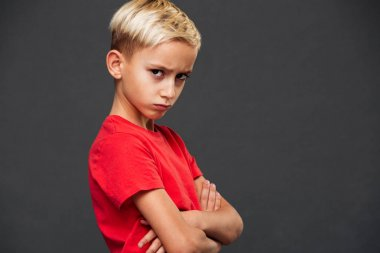Photo of angry little boy child standing isolated over grey background. Looking camera with arms crossed.