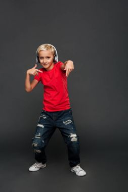 Picture of emotional little boy child standing isolated over grey background. Looking camera listening music with headphones dancing.