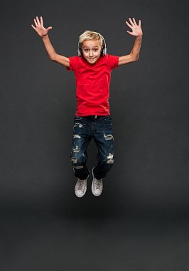 Image of excited little boy child jumping isolated over grey background. Looking camera listening music with headphones.