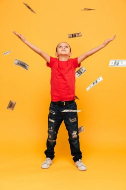 Image of concentrated little boy child standing isolated over yellow background. Looking aside over money.