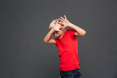 Image of screaming scared little boy child standing isolated over grey background. Looking camera.