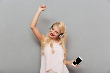 Portrait of a smiling girl listening to music with earphones