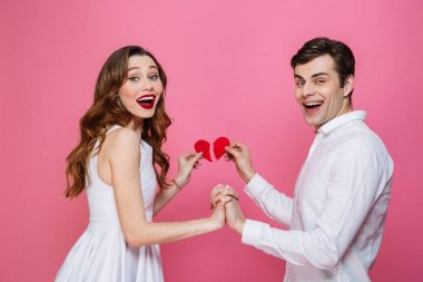 Happy loving couple holding two halves of heart