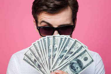 Serious handsome man wearing sunglasses holding money