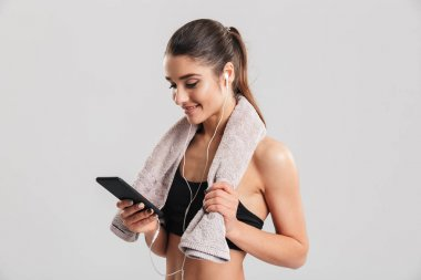 Portrait of young woman in gym posing with towel on neck and lis