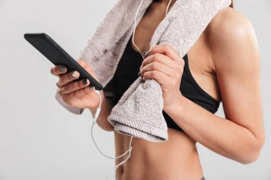 Cropped image of young woman in gym with towel on neck and liste