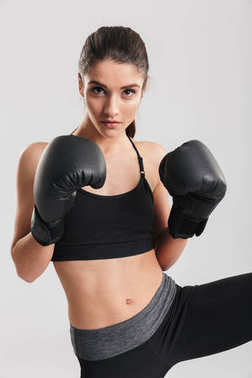 Concentrated brunette sportswoman training in boxing gloves while looking on camera over white background stock vector