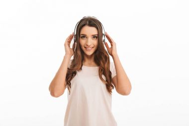 Smiling brunette woman in t-shirt listening music with headphones