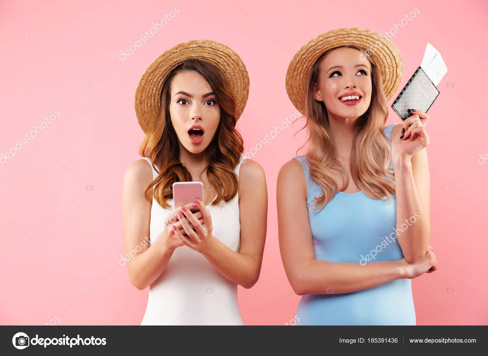 Dos preciosas mujeres felices en ropa de verano sonriendo mientras ...