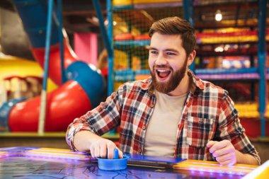 Smiling young man playing air hockey at Arcade centre stock vector