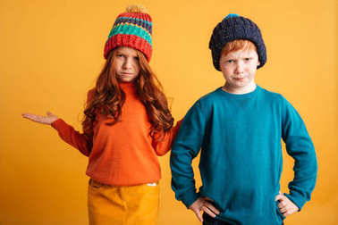 Two confused little redhead children wearing warm hats.