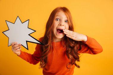 Shocked little redhead girl holding speech bubble.