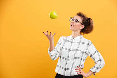 Portrait of healthy woman in plaid shirt throwing green apple up