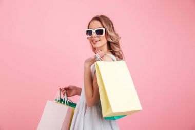 Happy young woman wearing sunglasses holding shopping bags.