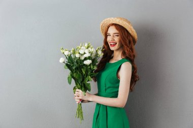 Redhead young cheerful woman with flowers.