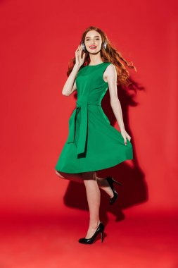 Redhead young happy girl in green dress
