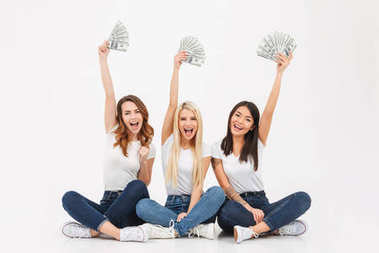 Three young excited pretty girls showing money.