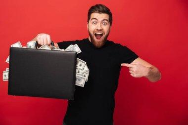 Bearded man holding suitcase full of money