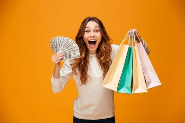 Excited screaming young lady holding shopping bags and money.