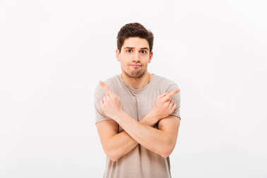 Image of indecisive man wearing beige t-shirt gesturing fingers aside with crossed arms on two copyspace options isolated over white background stock vector