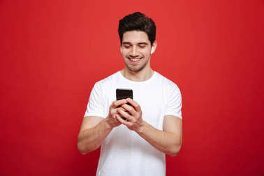 Portrait of a happy young man in white t-shirt listening to music with wireless earphones and mobile phone isolated over red background stock vector