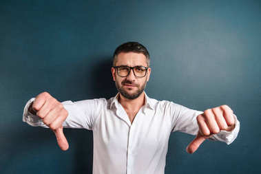 Sad man standing over dark blue background showing thumbs down.