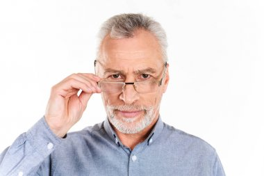 Serious man holding his glasses and looking camera isolated